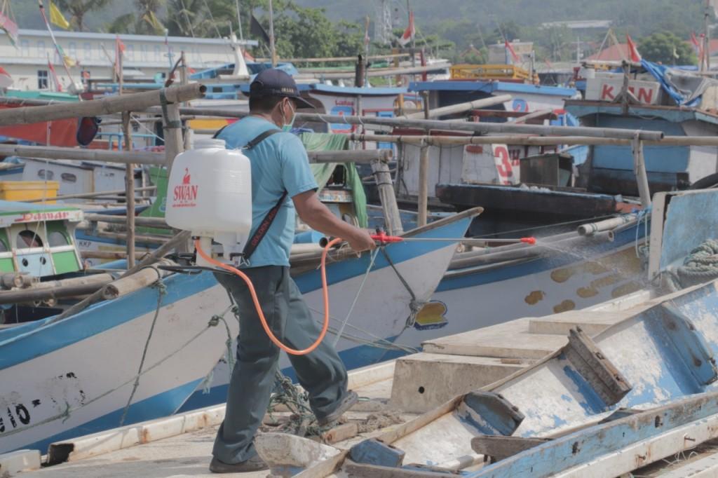 Petugas menyemprotkan disinfektan ke perahu nelayan (Foto: KKP)